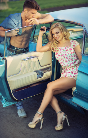 Graceful blond woman sitting in the retro car photo