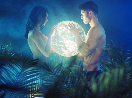 shirtless young couple holding shiny Earth