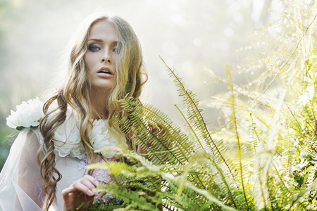 Beautiful blond woman next to the tropical fern