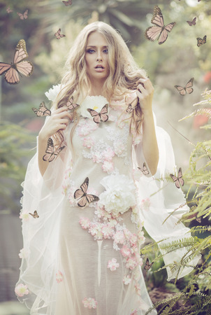 Portrhe young woman among the flying butterflies photo