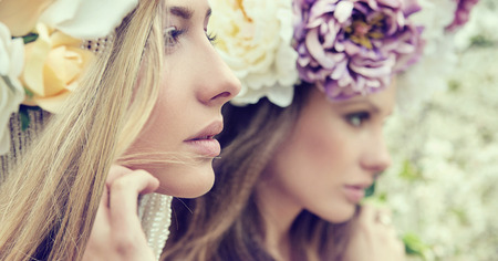 femmes souriantes: Portrait de deux femmes magnifiques avec des fleurs sauvages Banque d'images