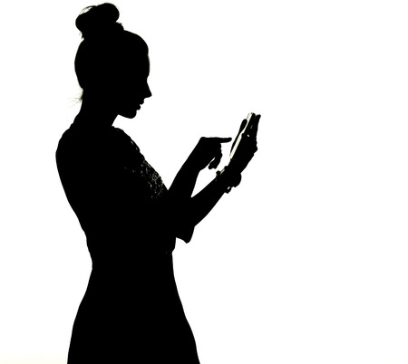 Silhouette di una signora uisng smartphone Archivio Fotografico - 28631905