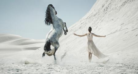 Mooie dame met wit paard in de woestijn Stockfoto