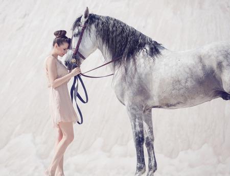 美しい若い女性はアラビアの馬を抱き締める