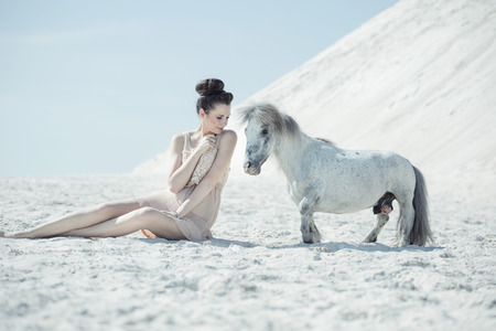 Charming woman playing with the pony photo