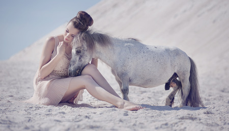 Pretty young woman hugging the white pony photo
