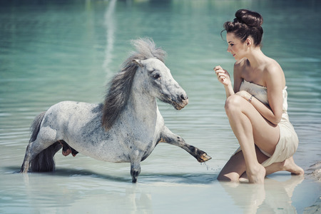 Alluring lady playing with the pony in the pool photo