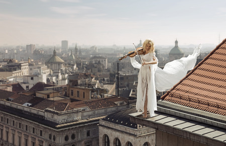 Lady playing the violin on the top of the edge of the roof Stock Photo
