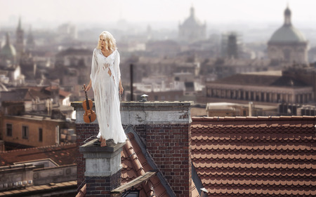Blonde standing on the dirty chimney with the violin