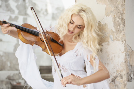 Blond cute woman playing the violin photo
