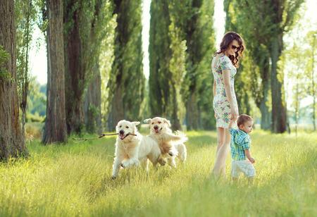 mujer con perro: Ni�o que juega con los perros mam� y felices Foto de archivo