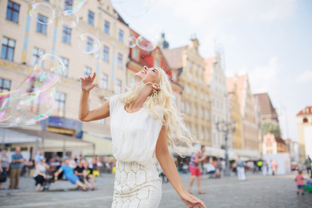 Alluring blond lady having a grat fun with the soap bubbles photo