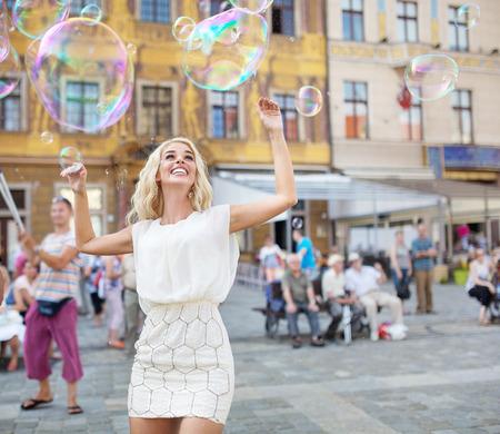 poses de modelos: Señora joven alegre que la captura de las pompas de jabón