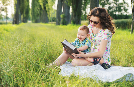 baby hairstyle: Mother with curly hairstyle reading fairy tales for cute  baby Stock Photo