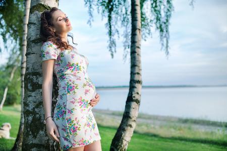 happy pregnant: Mujer embarazada realxed apoyado en el árbol Foto de archivo