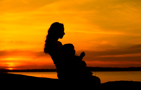 Mother and baby looking at the sunset photo