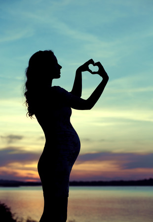 Prgenant mother making the heart sign photo