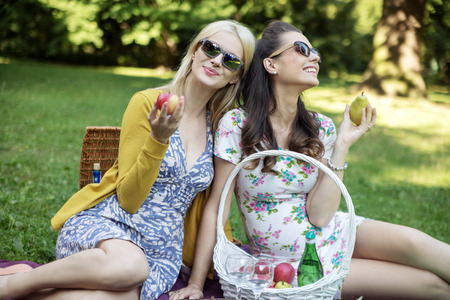Glad women eating tasty juicy fruit photo