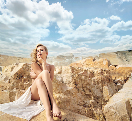 Sensual blond woman with the beautiful landscape behind photo