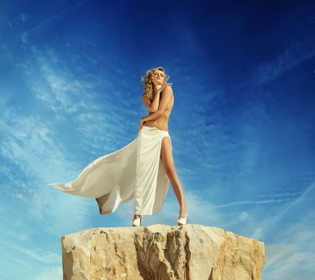 Half-naked blond lady posing on the top of the mountain photo
