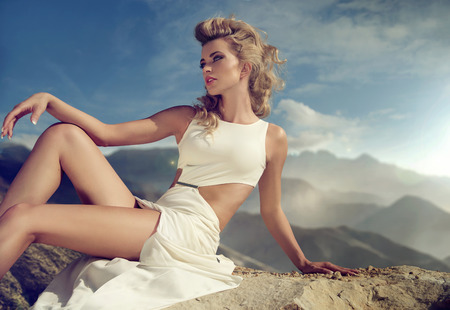 modelo desnuda: Curly se�ora de pelo sentado en la roca Foto de archivo