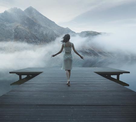 Donna di fascino che cammina sul pontile di legno Archivio Fotografico