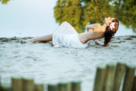 Alluring lady lying on the white sand photo