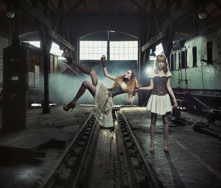 Two sensual witches in the old and empty railway station photo