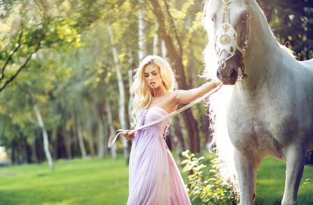 Blonde nimf walking met een wit paard