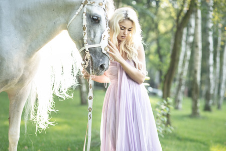 Blond cute woman with a white  horse