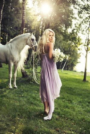 femme et cheval: Nymphe blonde avec des fleurs et cheval blanc Banque d'images