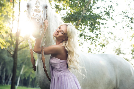 woman horse: Satisfied woman hugging the white horse