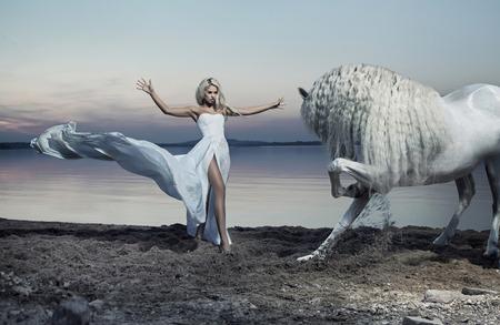魅力的な女性の白い馬を飼いならす