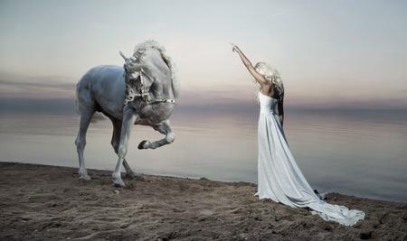 白い馬の反対側に立っている格好良い女性