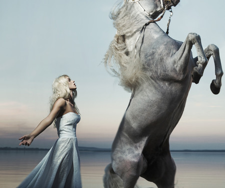 Blond nymph posing with the majestic horse photo