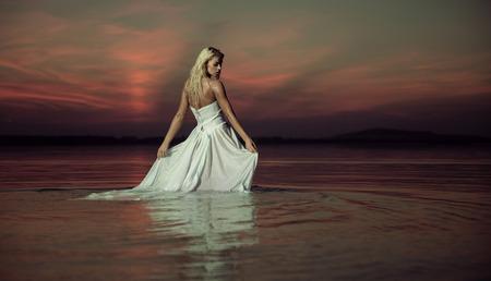 Sensual lady dancing in the lake photo