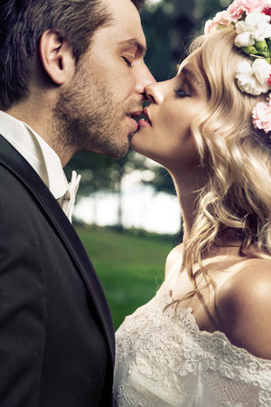 groom: Portrait of the young kissing marriage couple