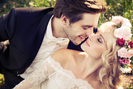 Romantic scene of kissing marriage couple photo