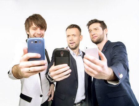 A few guys uisng their new smart phones Stock Photo