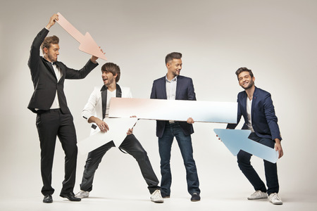 Amused guys holding arrows and boards photo