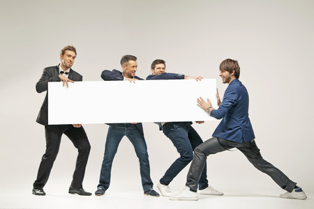Group of handsome men pushing a board photo