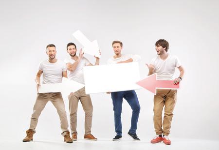 Group of joyful guys holding white symbols photo