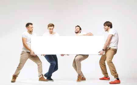Casual clothed boys carrying huge billboard photo