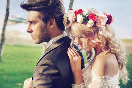 Stoere bruidegom met zijn delicate jonge vrouw Stockfoto