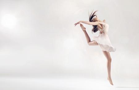 Pretty female ballet dancer in hard jump figure