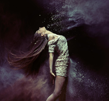 Young ballet dancer dancing with the colorful dust