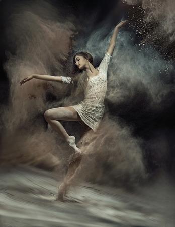 백그라운드에서 먼지와 함께 예쁜 발레 댄서 스톡 콘텐츠