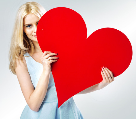 Cute blond girl hiding behind the paper heart