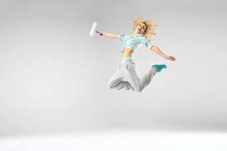 paintroller: Woman jumping and holding a paintroller Stock Photo