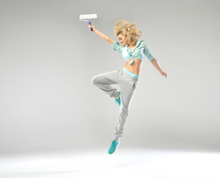 paint roller: Fabulous shapely woman jumping with paint roller